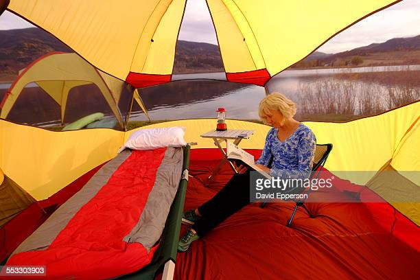 Women tent camping by mountain lake