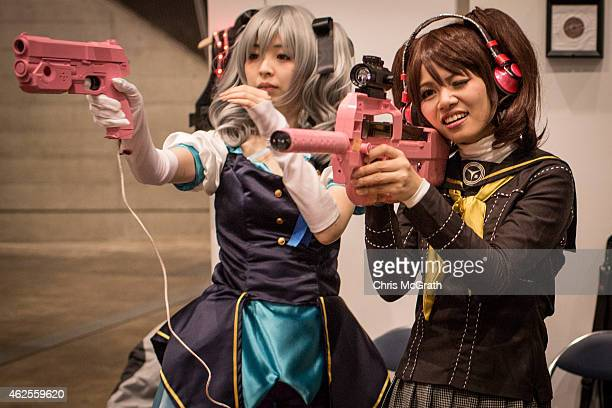 Women test out video game guns at a booth during Game Party Japan 2015 at the Makuhari Messe on January 31 2015 in Tokyo Japan The event widely known...