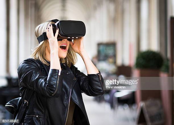 women testing virtual reality simulator on the street - head mounted display stock photos and pictures