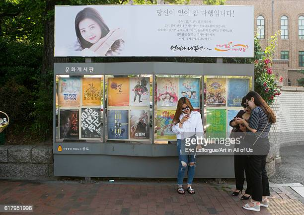 Women texting on their mobile phones in front of movie poster in the street national capital area seoul South Korea on June 5 2016 in Seoul South...