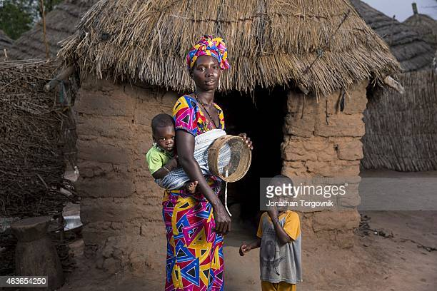 A women that took part in the TOSTAN Community Empowerment Program with her children near her home During the Community Empowerment Program women...