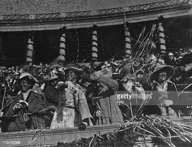 Women throw confetti during a Harvard University commencement ceremony, Harvard Stadium, circa 1915. . This image has been digitally retouched.