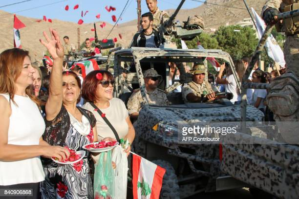 Women throw out flower petals as Lebanese Army soldiers drive by during a celebration of their return from battling Islamic State group jihadists on...