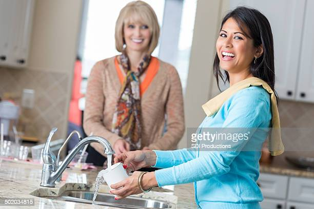 women tidying kitchen after party in modern home - cleaning after party stock pictures, royalty-free photos & images