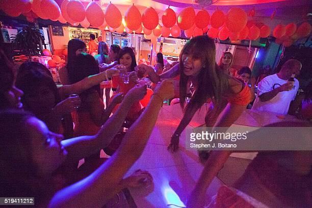 Women toast with shots at a bar girl bar in Lamai Beach on Ko Samui Island