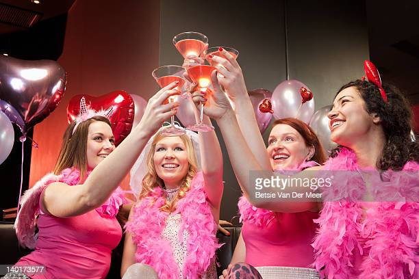 Women toasting cocktails at hen night party.