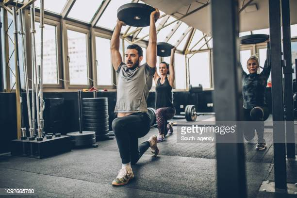 women together with fitness coach in gym - cross training stock pictures, royalty-free photos & images
