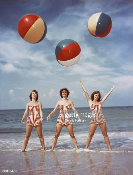 Women tossing beach balls in ocean
