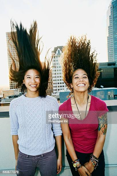 Women tossing their hair on urban rooftop
