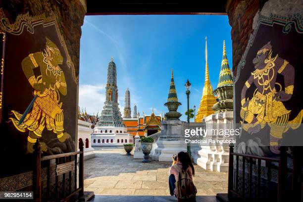 "women tourists are taking a photo of the temple and sit in front of the hanuman statue of thai art on the door at wat phra kaew or the temple of the emerald buddha in bangkok, thailand.""n - grand palace bangkok stock pictures, royalty-free photos & images"