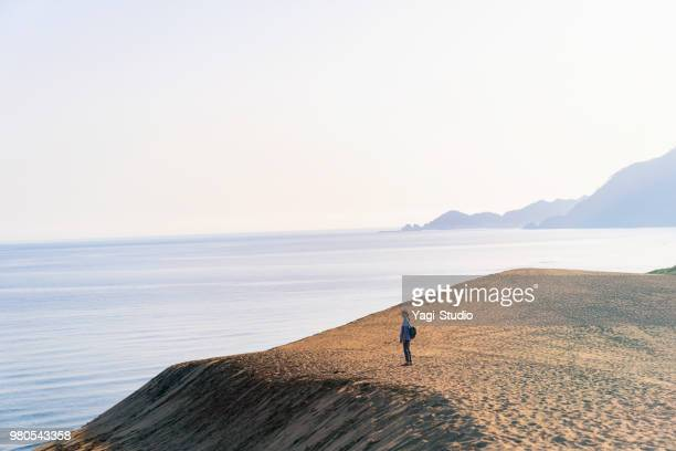 women traveler walking in tha sand dune looking at the sea - tottori prefecture stock photos and pictures