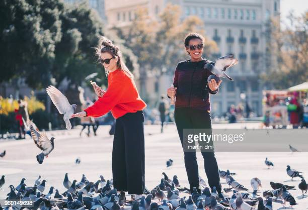Women traveling in Europe and feeding pigeons in Barcelona