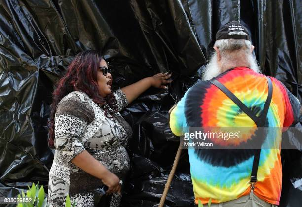 A women tries to stop John Miska from cutting off the black tarp that was put over the statue of Confederate Gen Robert E Lee that stands in the...