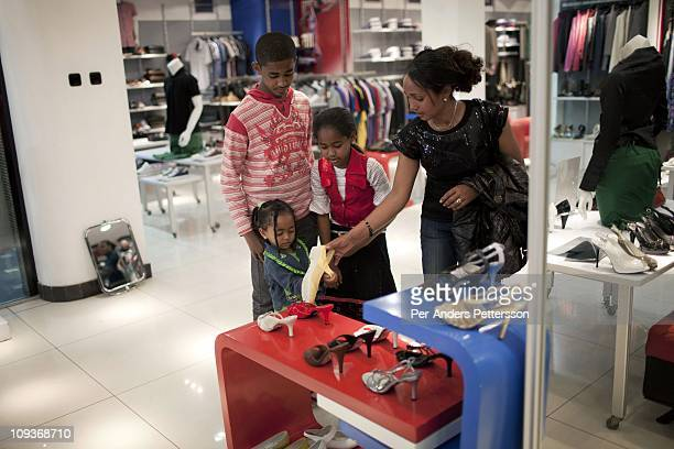 Women try shoes in an upmarket clothing shop for women on November 13 2010 in a shopping mall in Addis Ababa Ethiopia Some people can afford to buy...