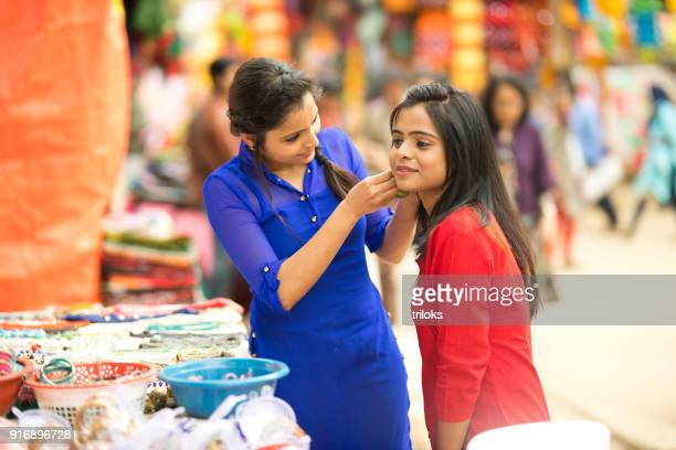 Women trying on earring at street market stall