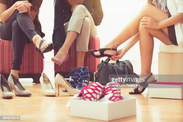 Women trying on shoes in store