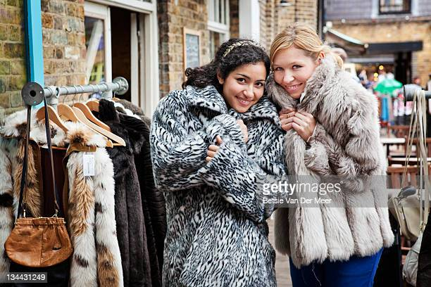 women trying on vintage fack fur coats. - fur coat stock pictures, royalty-free photos & images