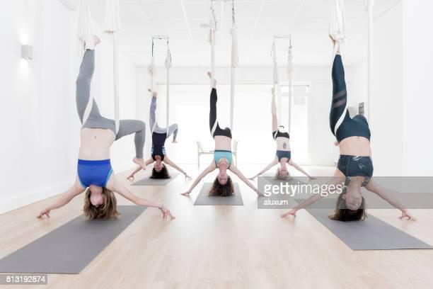 Women upside down during aerial yoga class