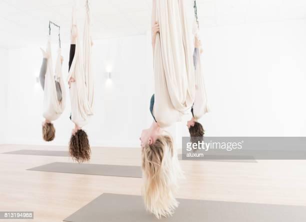 Women upside down in aerial yoga class