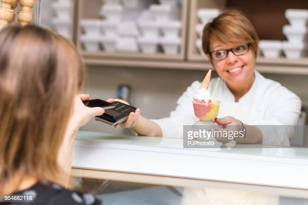 Women use contactless payment in an ice cream shop - focus on pad