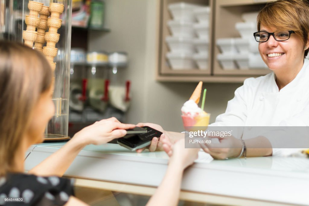 Women use contactless payment in an ice cream shop : Foto stock
