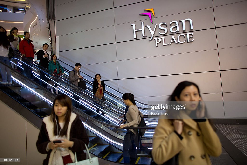 Women use mobile phones as customers ride on escalators at Hysan Development Co.'s Hysan Place mall in the Causeway Bay district of Hong Kong, China, on Monday, March 4, 2013. Hysan is scheduled to release earnings on March 6. Photographer: Lam Yik Fei/Bloomberg via Getty Images