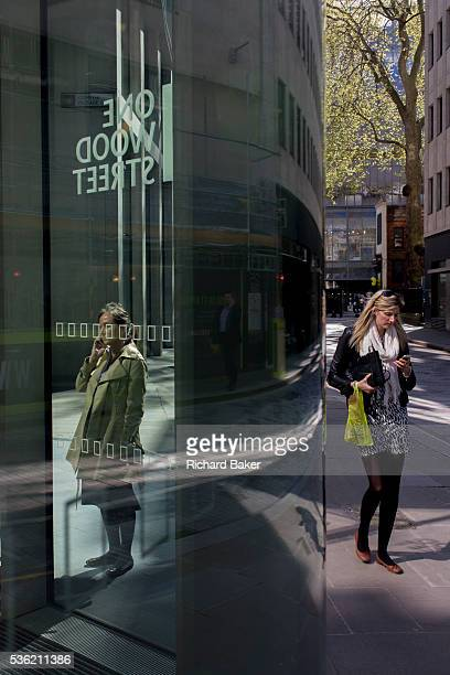 Women use smartphones outside a corporate office entrance with city reflections in glass As strangers the ladies don't know each other and the one on...