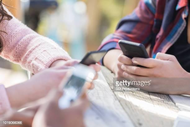 as mulheres usam smartphones, ignorando os outros - filtro de pós produção automática - fotografias e filmes do acervo