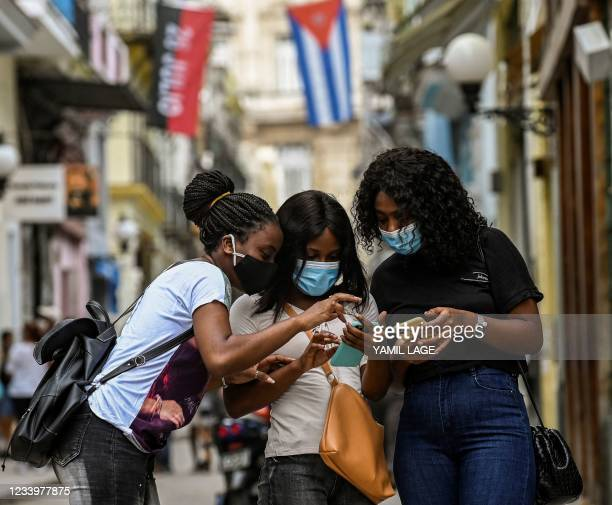 Women use their phones in a street of Havana, on July 14, 2021. - Cuban authorities restored internet access on Wednesday following three days of...