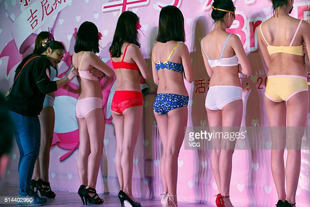 A women uses one hand to unbutton models's bras during a competition at a shopping mall on March 8 2016 in Liuzhou Guangxi Zhuang Autonomous Region...