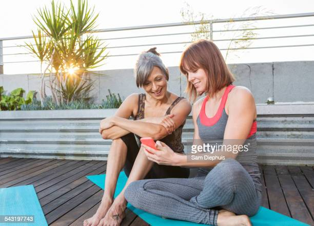 Women using cell phone on exercise mat