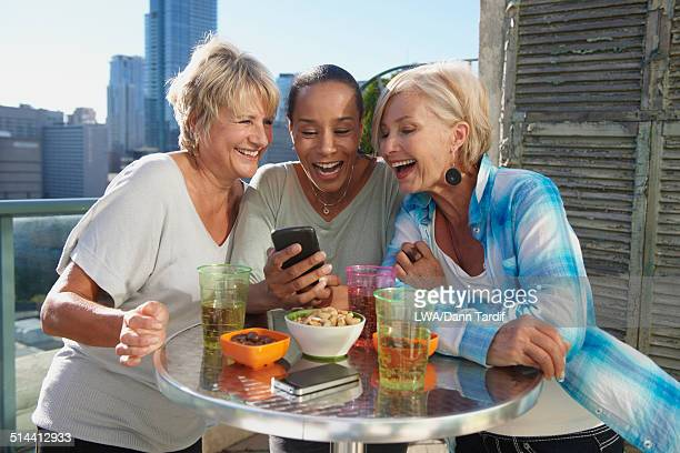 Women using cell phone together at rooftop bar