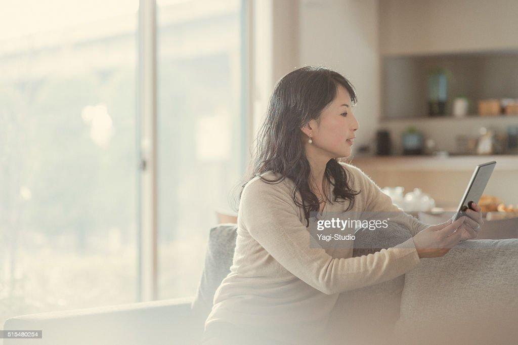 を使用して女性デジタルタブレットとに座っているソファー : ストックフォト