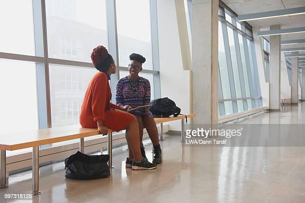 Women using digital tablet in hallway