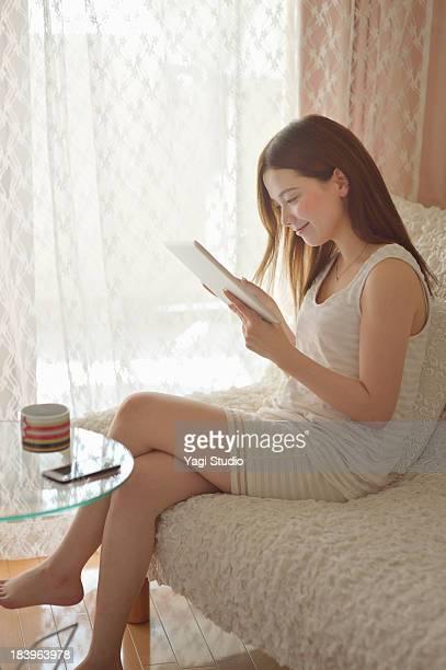 Women using digital tablet on the sofa.