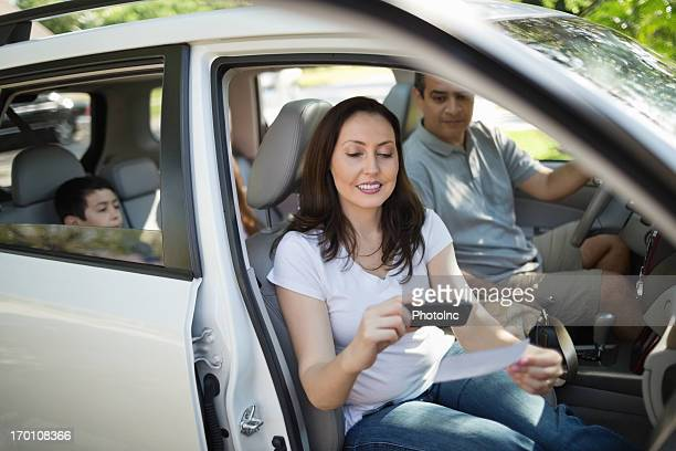 Women Using Smart Phone To Deposit Check In Car