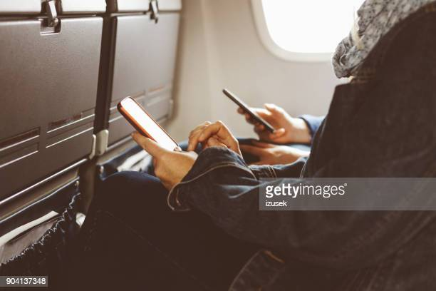 Women using smart phone while travelling by airplane