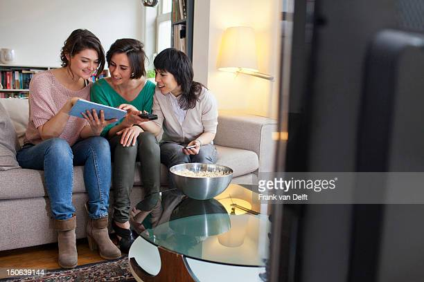 Women using tablet computer on sofa