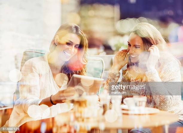 Women using tablet pc at  sidewalk cafe
