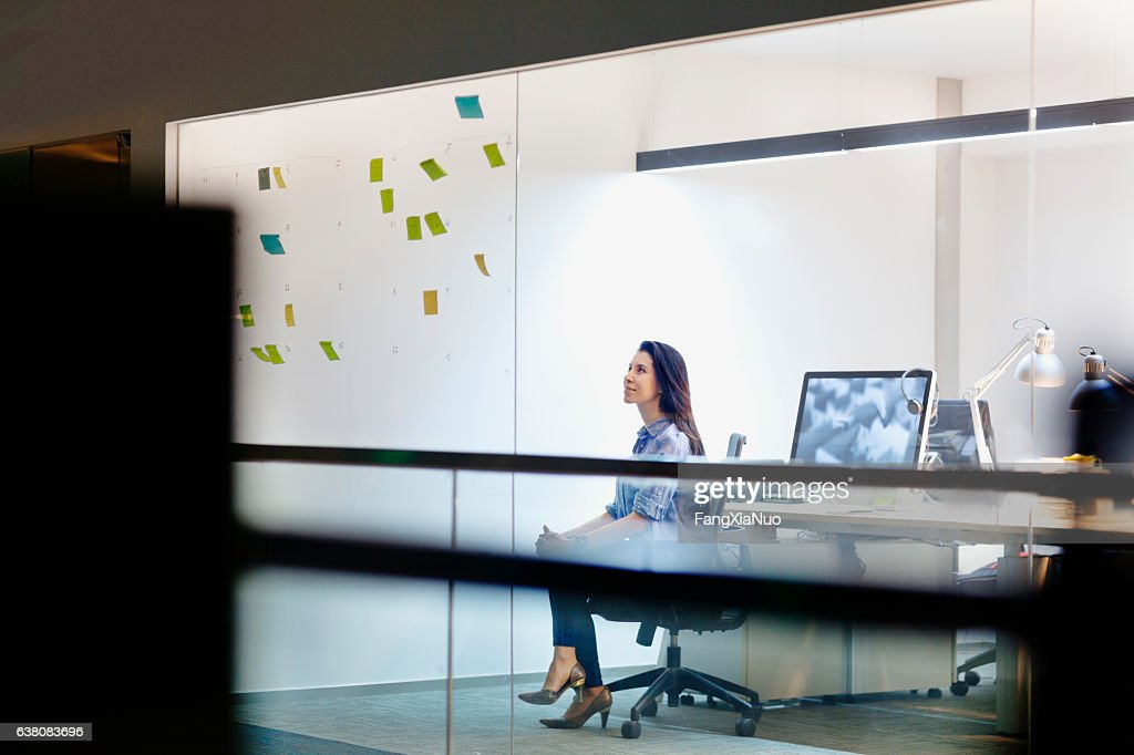 Women viewing ideas on notes in design studio at night : Stock Photo