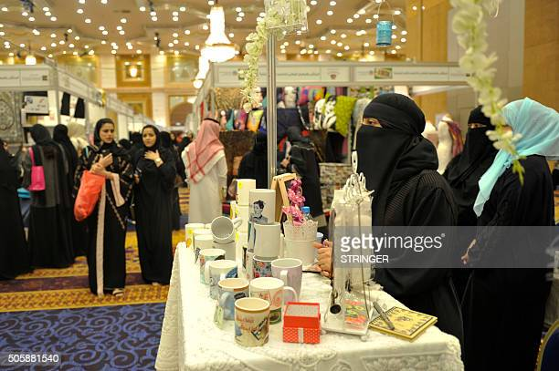 Women visit stands during a fair gathering families selling traditional crafts clothes and food on January 20 2016 in the Saudi Red Sea port of...