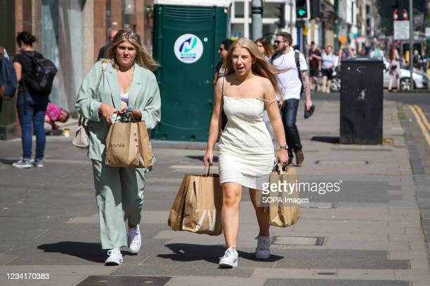 Women visiting Edinburgh walk on the street with Primark shopping bags. Number of tourists visiting Edinburgh is low due to Covid-19 and lockdowns.