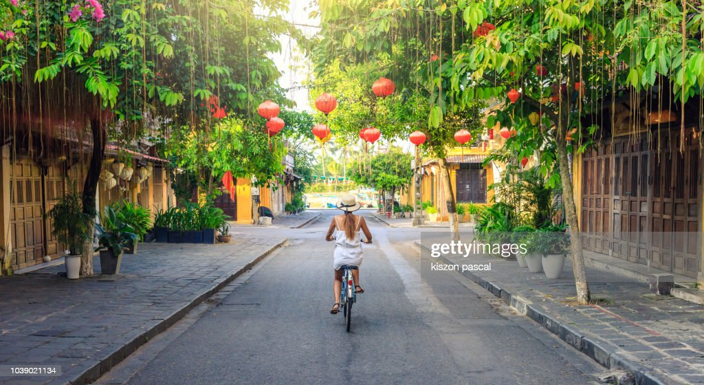 Women visiting the old city of Hoi An in Vietnam by bike during morning : Stockfoto