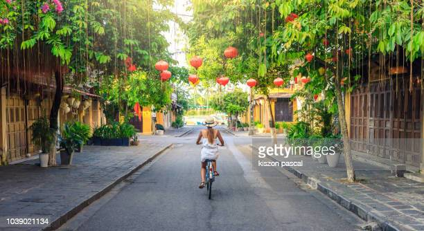 women visiting the old city of hoi an in vietnam by bike during morning - vietnam stockfoto's en -beelden