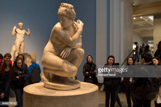 Women visitors admire the Hellenistic Crouching Aphrodite sculpture on 28th February 2017 in the British Museum London England