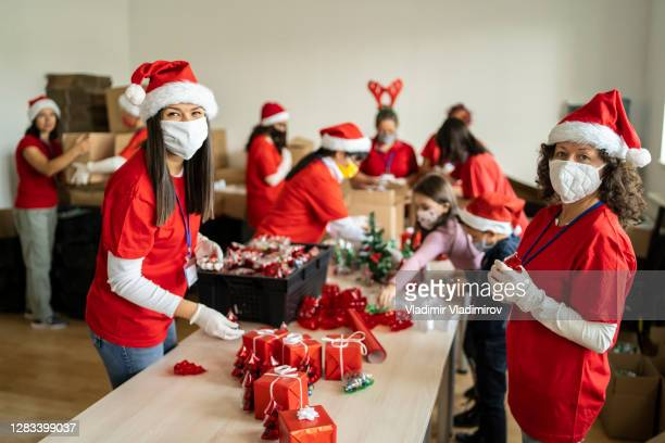 women volunteering by preparation of christmas presents for poor people in time of pandemic - volunteer stock pictures, royalty-free photos & images