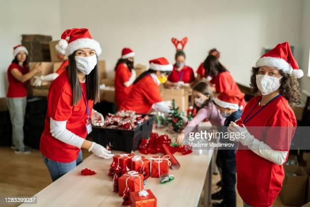 frauen ehrenamtlich durch vorbereitung von weihnachtsgeschenken für arme menschen in zeiten der pandemie - spende für wohltätige zwecke stock-fotos und bilder