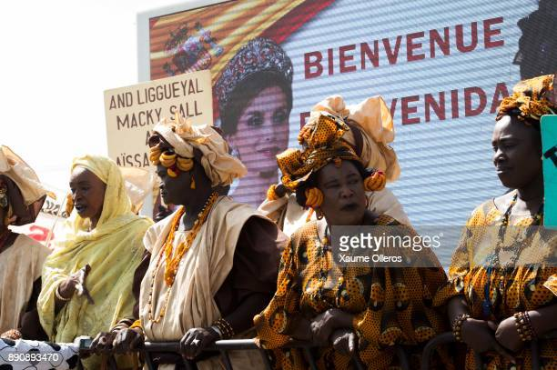 Women wait as a Letizia of Spain banner is displayed prior to her arrival to a lunch offered by first lady Marieme Faye Sall on December 12 2017 in...