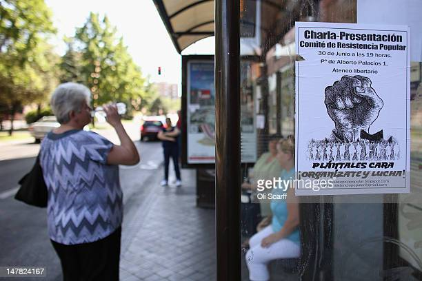 Women wait at a bus stop behind a poster advertising a protest rally in the suburb of Villaverde on July 4 2012 in Madrid Spain Despite having the...