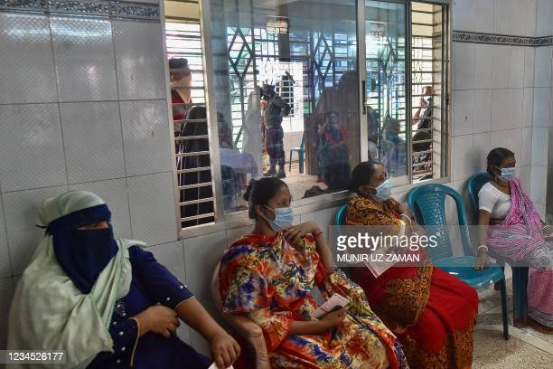 Women wait at the observation area after being inoculated with the Sinopharm Covid-19 coronavirus vaccine during a mass vaccination camp at Kholamora...